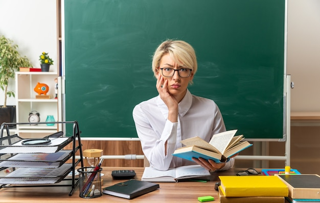 カメラを見て顔に手を保ちながら開いた本を保持している教室で学校の道具を持って机に座って眼鏡をかけている眉をひそめている若い金髪の女教師