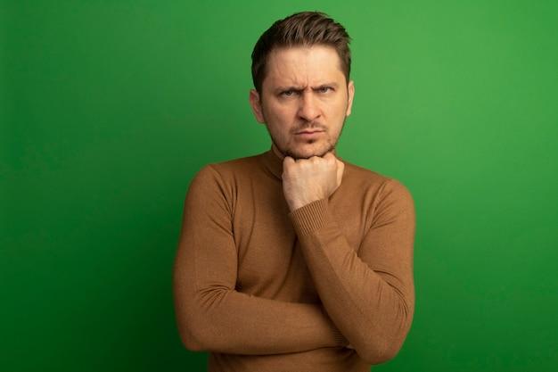 コピースペースで緑の壁に隔離された正面を見てあごの下に手を置く眉をひそめている若いブロンドのハンサムな男