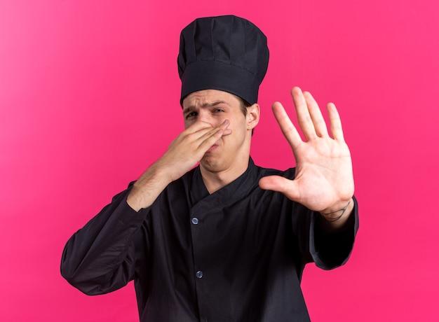 Хмурый молодой блондин мужчина-повар в униформе шеф-повара и кепке делает жест неприятного запаха, глядя в камеру, делая жест остановки, изолированный на розовой стене