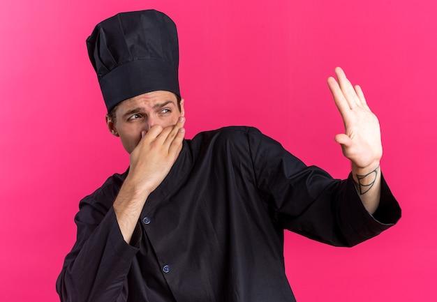 Хмурый молодой блондин мужчина-повар в униформе шеф-повара и кепке делает жест неприятного запаха, глядя в сторону, делая жест остановки, изолированный на розовой стене