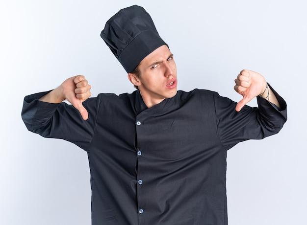 眉をひそめている若いブロンドの男性料理人シェフの制服と白い壁に隔離された親指を下に表示しているカメラを見てキャップ