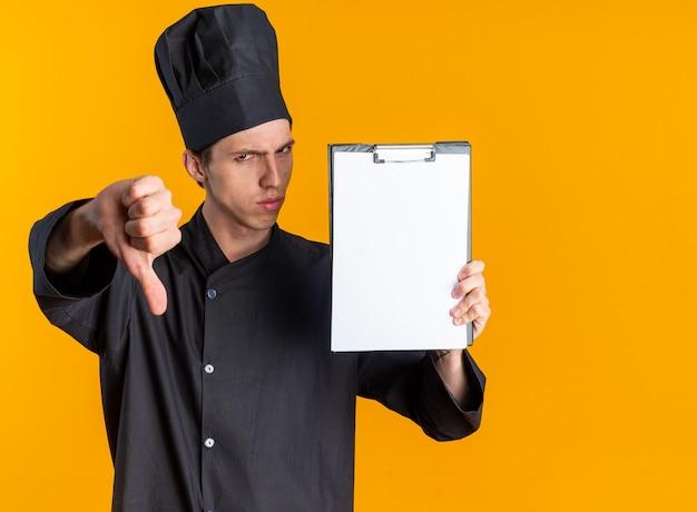 Хмурый молодой блондин мужчина-повар в униформе шеф-повара и кепке показывает буфер обмена и большой палец вниз, глядя в камеру, изолированную на оранжевой стене с копией пространства