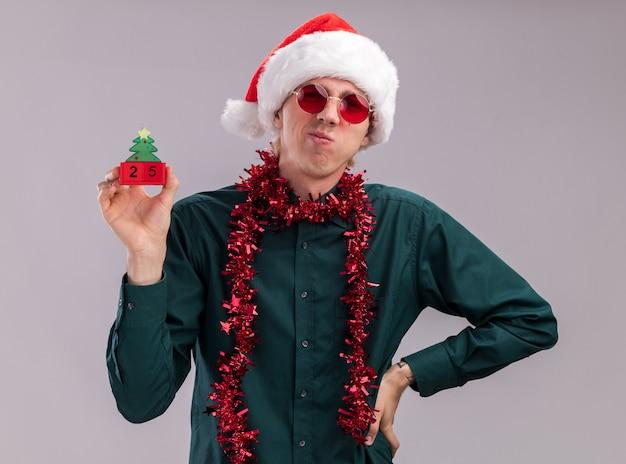 白い背景で隔離の腰に手を保持しているカメラを見て日付とクリスマスツリーのおもちゃを保持している首の周りに見掛け倒しの花輪とサンタの帽子とメガネを身に着けている眉をひそめている若いブロンドの男