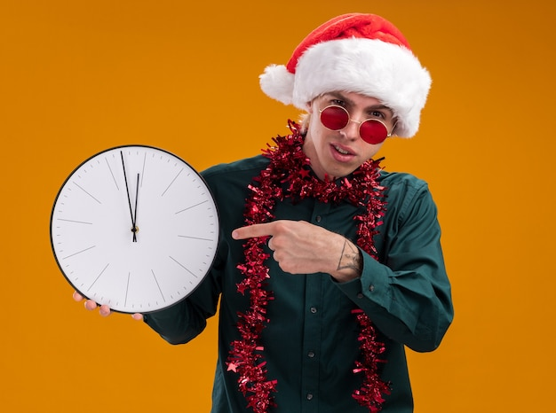 Frowning young blonde man wearing santa hat and glasses with tinsel garland around neck holding and pointing at clock looking at camera isolated on orange background