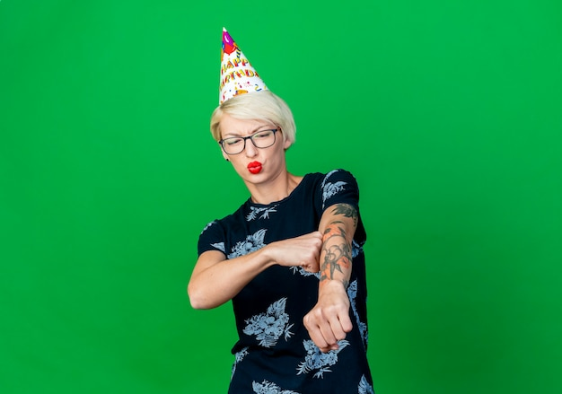 Frowning young blonde party girl wearing glasses and birthday cap stretching out fist touching arm with fist looking at arm isolated on green background with copy space