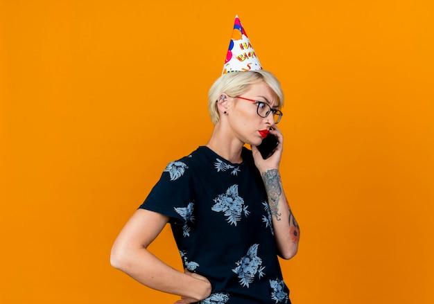 Accigliata e giovane bionda party girl con gli occhiali e cappello di compleanno parlando al telefono guardando verso il basso tenendo la mano sulla vita isolata su sfondo arancione con spazio di copia