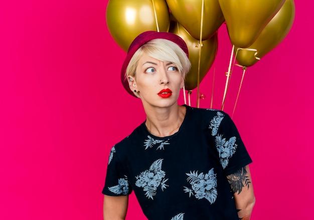 コピースペースで深紅色の背景に分離された側を見て風船の前に立っているパーティー帽子をかぶって眉をひそめている若いブロンドのパーティーの女の子