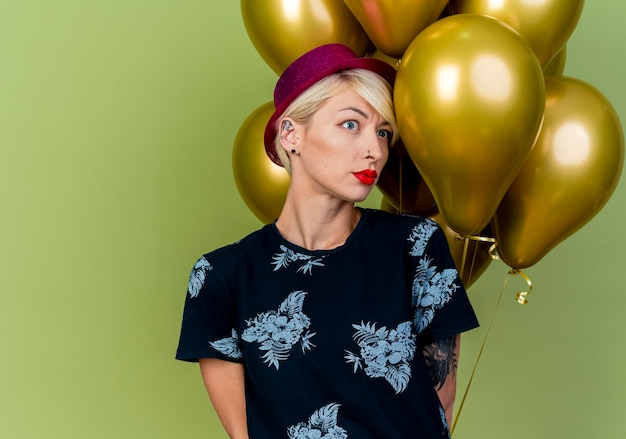 Frowning young blonde party woman wearing party hat standing in front of balloons looking at side keeping hands behind back isolated on olive green wall with copy space
