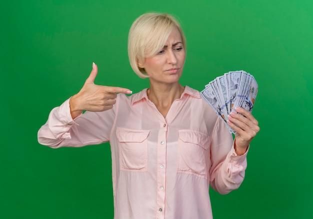 Aggrottando le sopracciglia giovane bionda donna slava che tiene guardando e facendo gesto di pistola a soldi isolato su sfondo verde