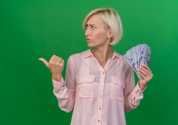 Accigliata giovane bionda donna slava tenendo i soldi girando la testa a lato e indicando a lato isolato su sfondo verde con copia spazio