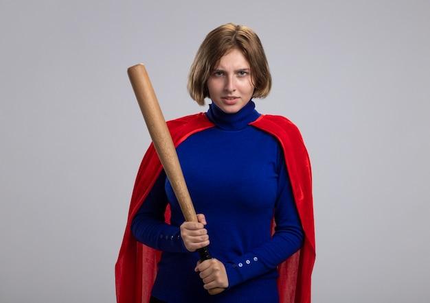 Accigliata giovane ragazza bionda del supereroe in mantello rosso che tiene la mazza da baseball isolata sulla parete bianca con lo spazio della copia