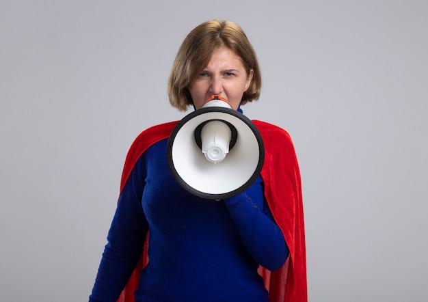 Accigliata giovane ragazza bionda del supereroe in mantello rosso parlando da altoparlante isolato sulla parete bianca con lo spazio della copia