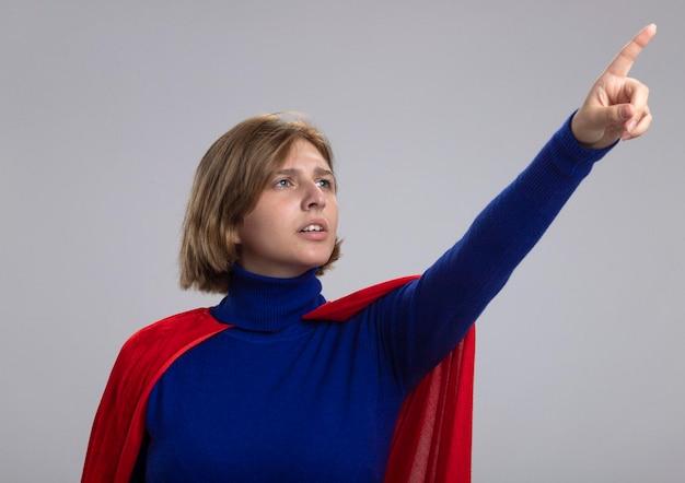 Aggrottando le sopracciglia giovane donna bionda del supereroe in mantello rosso alla ricerca e rivolto verso l'alto isolato sul muro bianco