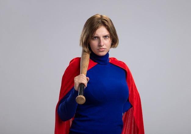Aggrottando le sopracciglia giovane superdonna bionda in mantello rosso che tiene la mazza da baseball sulla spalla guardando la parte anteriore isolata sul muro bianco