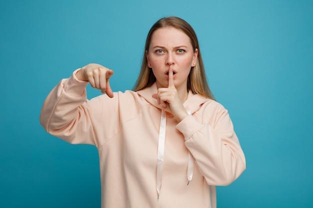 沈黙のジェスチャーをしているカメラを見て、指している眉をひそめている若いブロンドの女性