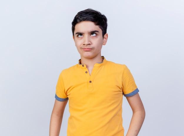 Хмурый молодой кавказский мальчик скрещивает глаза, глядя вверх изолированно на белом фоне с копией пространства