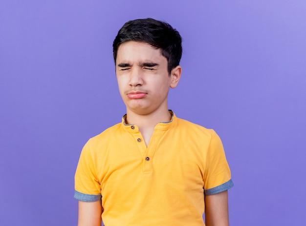 Хмурый молодой кавказский мальчик с закрытыми глазами, изолированные на фиолетовом фоне с копией пространства