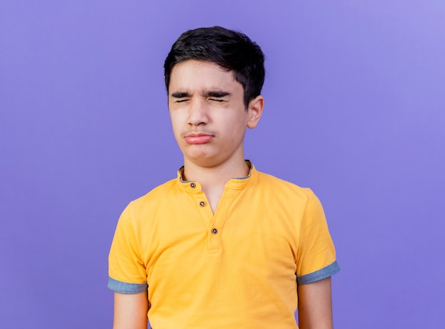 Frowning young caucasian boy with closed eyes isolated on purple background with copy space