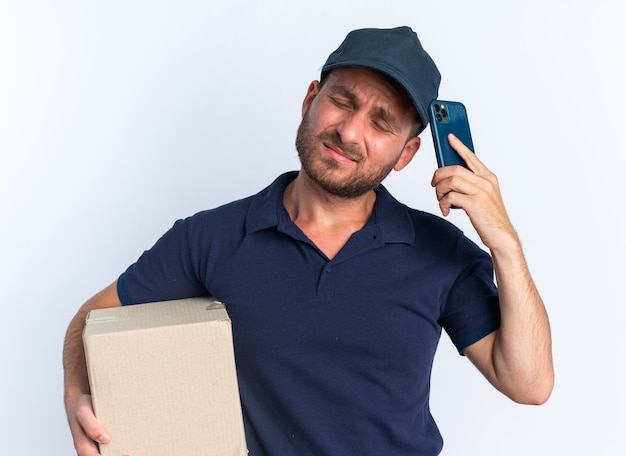 Frowning young caucasian delivery man in blue uniform and cap holding cardboard box touching head with mobile phone with closed eyes isolated on white wall