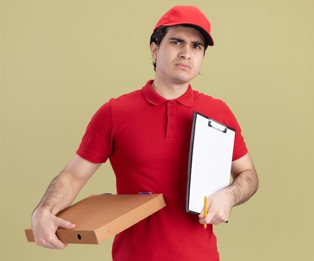Accigliato giovane fattorino caucasico in uniforme blu e berretto che tiene un pacchetto di pizza e appunti con matita isolato su parete verde oliva