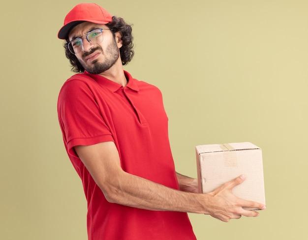 올리브 녹색 벽에 격리된 카드박스를 들고 프로필 보기에 서 있는 안경을 쓰고 빨간 제복을 입은 젊은 백인 배달원