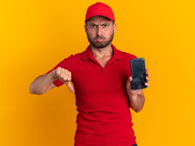 Frowning young caucasian delivery man in red uniform and cap looking at camera showing mobile phone and thumb down isolated on orange wall