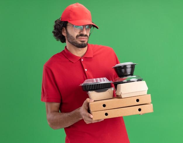 Accigliato giovane fattorino caucasico in uniforme rossa e berretto con gli occhiali che tengono in mano e guardano i pacchetti di pizza