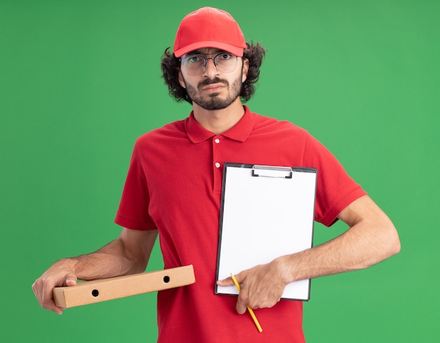 Frowning young caucasian delivery man in red uniform and cap wearing glasses holding pizza package pencil showing clipboard to camera  isolated on green wall