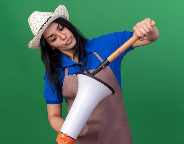 Нахмурившись, молодая кавказская девушка-садовник в униформе и шляпе трогает спикера с граблями, глядя на спикера, изолированного на зеленой стене