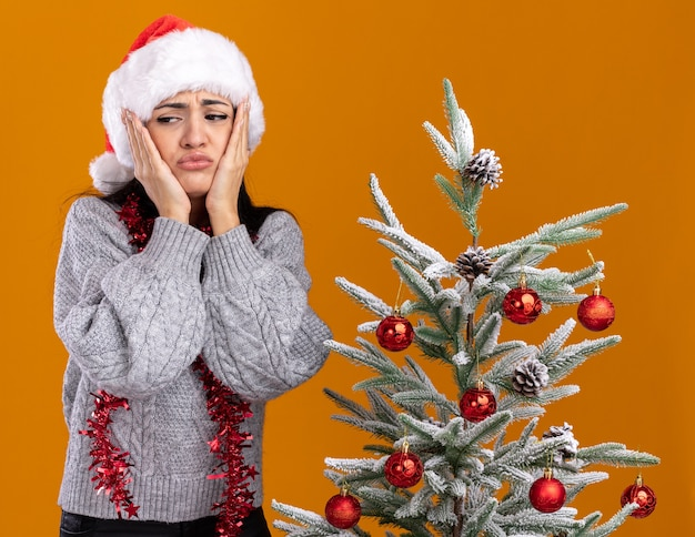 Frowning young caucasian girl wearing christmas hat and tinsel garland around neck standing near decorated christmas tree keeping hands on face looking at side isolated on orange background