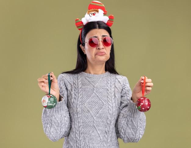 Accigliata giovane ragazza caucasica indossando la fascia di babbo natale con gli occhiali che tengono le bagattelle di natale che guarda l'obbiettivo isolato su sfondo verde oliva