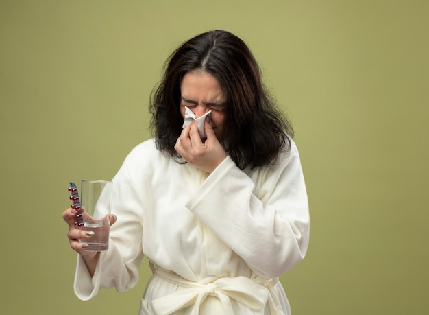 Frowning young caucasian ill girl wearing robe holding pack of medical pills glass of water and wiping nose with napkin with closed eyes isolated on olive green background with copy space