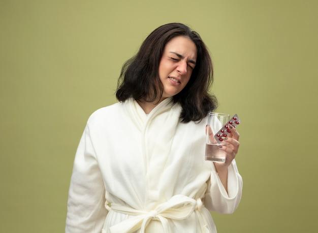 コピースペースでオリーブグリーンの背景に分離された目を閉じて医療薬のパックと水のガラスを保持しているローブを着て眉をひそめている若い白人の病気の女の子