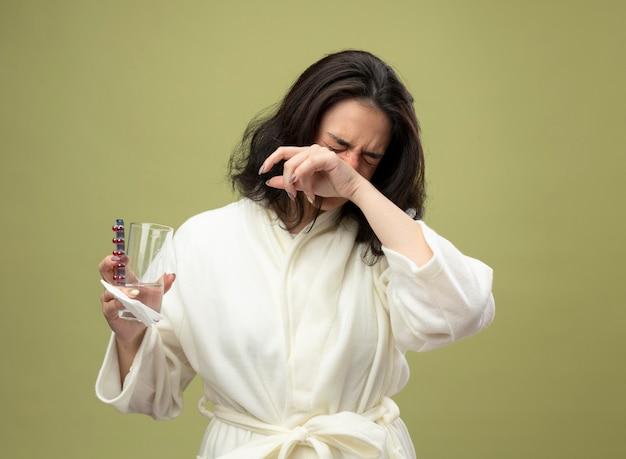 Нахмурившаяся молодая кавказская больная девушка в халате держит упаковку медицинских таблеток, стакан воды и салфетку, держа руку на носу с закрытыми глазами, изолированными на оливково-зеленом фоне