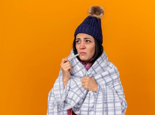 Нахмурившаяся молодая кавказская больная девушка в зимней шапке и шарфе, завернутая в плед, держит во рту термометр, хватает плед, глядя в сторону, изолированную на оранжевом фоне с копией пространства