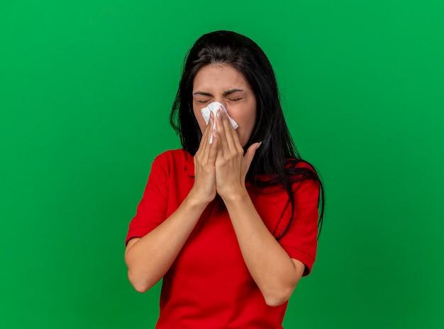 コピースペースのある緑の壁に隔離された目を閉じてナプキンで鼻を拭く眉をひそめている若い白人の病気の女の子