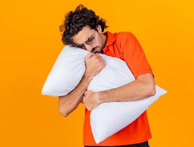 Accigliato giovane indoeuropeo uomo malato con gli occhiali che abbraccia cuscino mettendo la testa su di esso con gli occhi chiusi isolati su sfondo arancione
