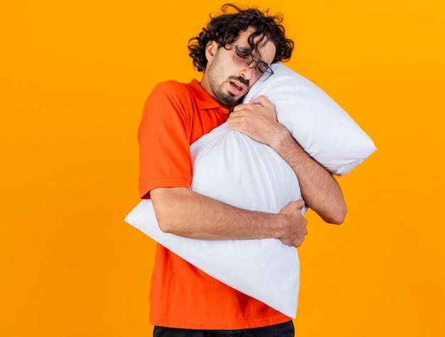 Accigliato giovane indoeuropeo uomo malato con gli occhiali che abbraccia cuscino toccando il viso con gli occhi chiusi isolato su sfondo arancione con spazio di copia