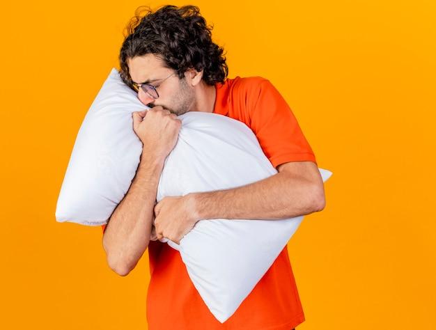 Хмурый молодой кавказский больной в очках обнимает подушку, поворачивая голову в сторону с закрытыми глазами, изолированными на оранжевом фоне с копией пространства