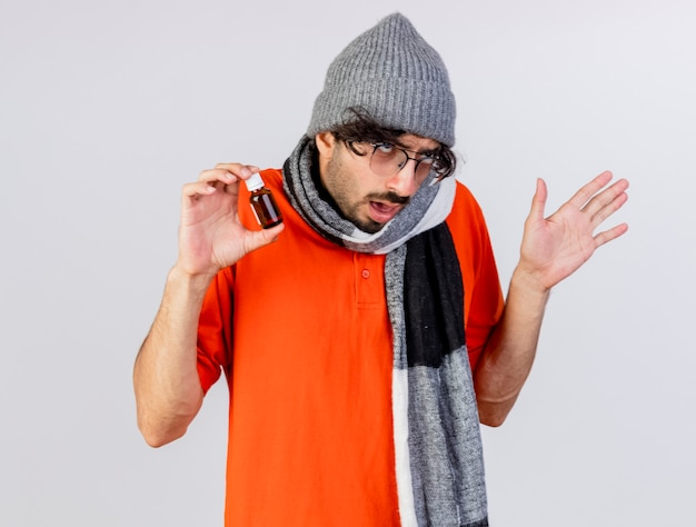 Frowning young caucasian ill man wearing glasses winter hat and scarf holding medicament in glass looking at side keeping hand in air isolated on white background