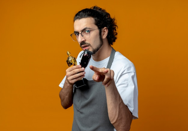 Frowning young caucasian male barber wearing glasses and wavy hair band in uniform holding winner cup and hair clippers doing i'm watching you gesture isolated on orange background with copy space