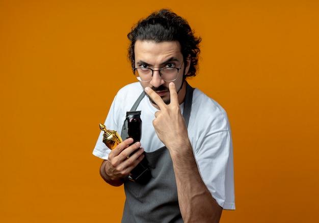 Accigliato giovane maschio caucasico barbiere con gli occhiali e fascia per capelli ondulati in uniforme che tiene tazza del vincitore e tosatrici facendo ti sto guardando gesto