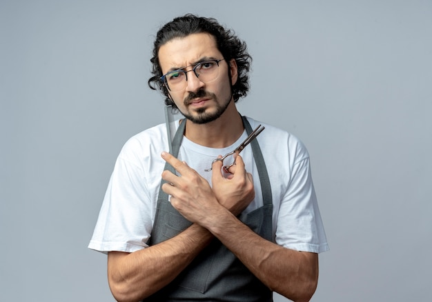 Frowning young caucasian male barber wearing glasses and wavy hair band in uniform keeping hands crossed and holding scissors and comb isolated on white background with copy space