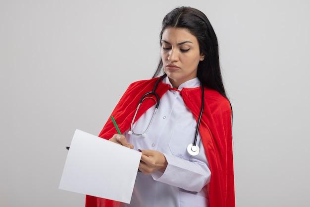 젊은 백인 슈퍼 히어로 소녀 복사 공간 흰색 배경에 고립 된 연필로 그것에 쓰기 클립 보드를 들고 청진기를 입고