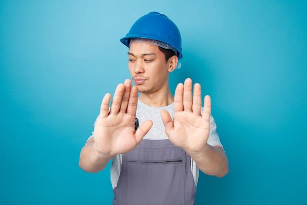 安全ヘルメットと制服を着て眉をひそめている若い建設労働者が拒否ジェスチャーをして見下ろしている