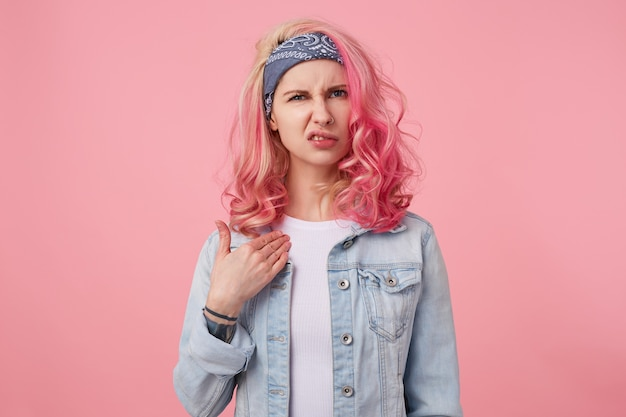 Нахмурившись, юная милая дама с розовыми волосами, агрессивно принимает критику и выглядит недовольным, указывает на себя и смотрит с отвращением, встает.