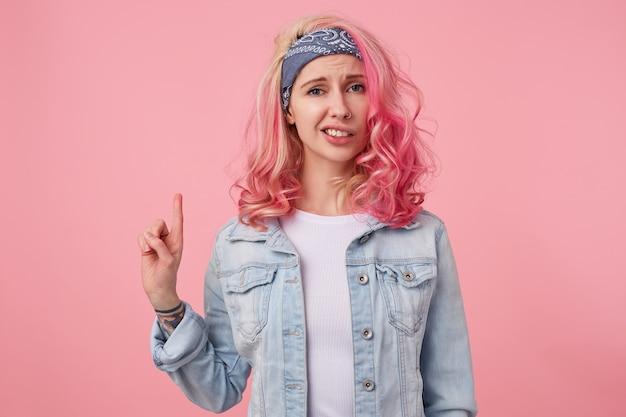 분홍색 머리를 가진 찡그린 귀여운 아가씨는 흰색 티셔츠와 데님 재킷을 입고 혐오감을 느끼며 서서 복사 공간에 손가락을 가리 킵니다.
