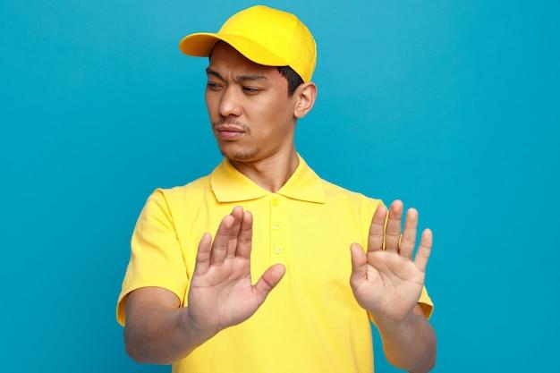 Accigliato giovane uomo di consegna che indossa l'uniforme e berretto guardando il lato facendo gesto di rifiuto