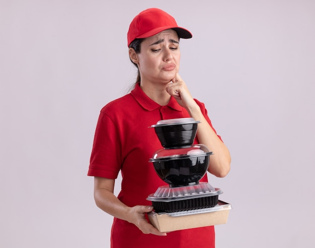 Frowning young delivery woman in uniform and cap holding and looking at paper food package and food containers touching chin isolated on white wall with copy space
