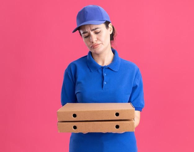 Giovane donna delle consegne accigliata in uniforme e berretto che tiene in mano e guarda i pacchetti di pizza